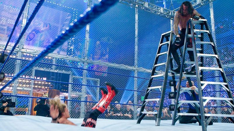 Undertaker giving a chokeslam to Edge, who went through the canvas.