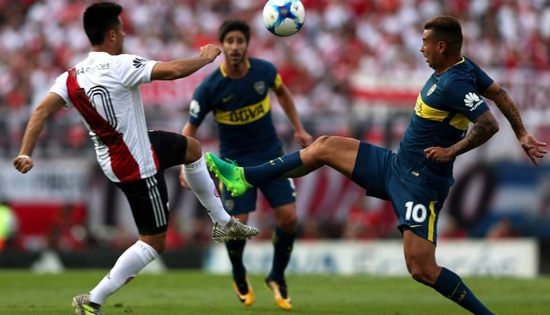 Players of River Plate (left) & Boca Juniors (right) vie for the ball during a recent derby game