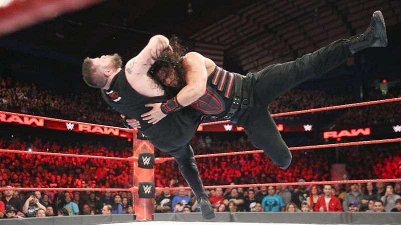 Roman Reigns delivering a spear to Kevin Owens