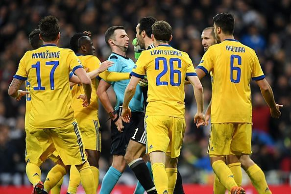 Juventus players confront referee Michael Oliver