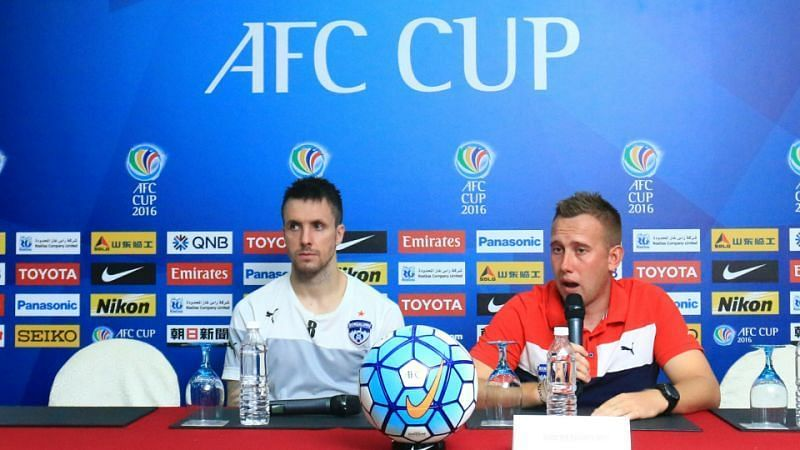 Michael Collins (left) attending a pre-match press conference for Bengaluru FC