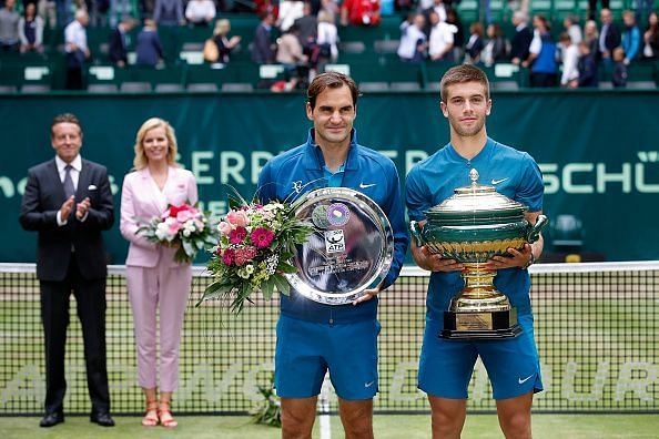 Roger Federer and Borna Coric pose with their plate and trophy, respectively at the Gerry Weber Open 2018.