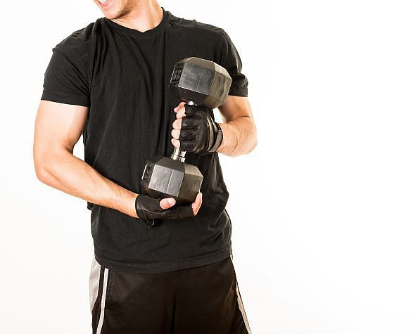 Physical activity: Young adult exercising with a 25 pounds...