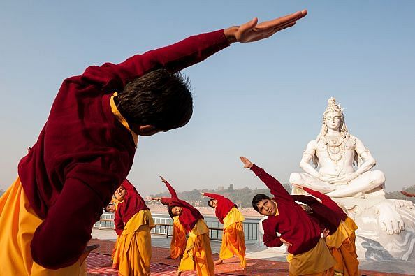 Young boys practice yoga along the Ganges River in Rishikesh, India...