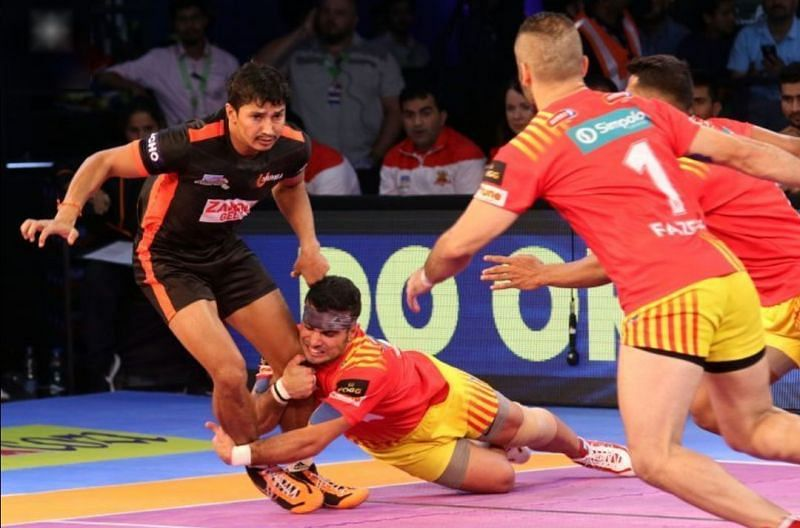 Abozar attempting a diving ankle hold over Mumba