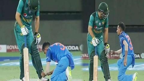 Yujvendra Chahal tying shoe laces of Usman Khan