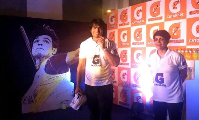 Neeraj Chopra and Mandira Bedi share a light moment on stage at the Welcome event