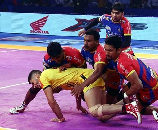यूपी योद्धा के खिलाड़ी राहुल चौधरी को रोकते हुए