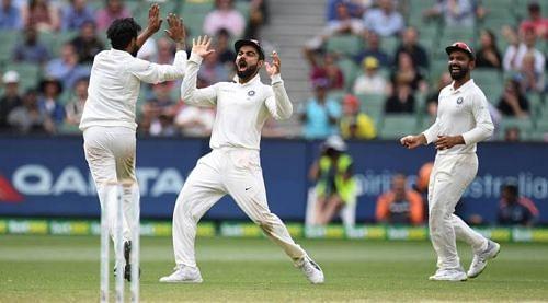 Virat Kohli (C) and Ravindra Jadeja celebrate a wicket