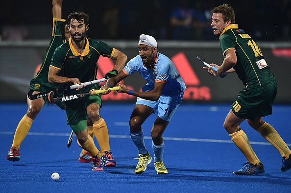 South African players vie for the ball against India in their first match of the Hockey World Cup