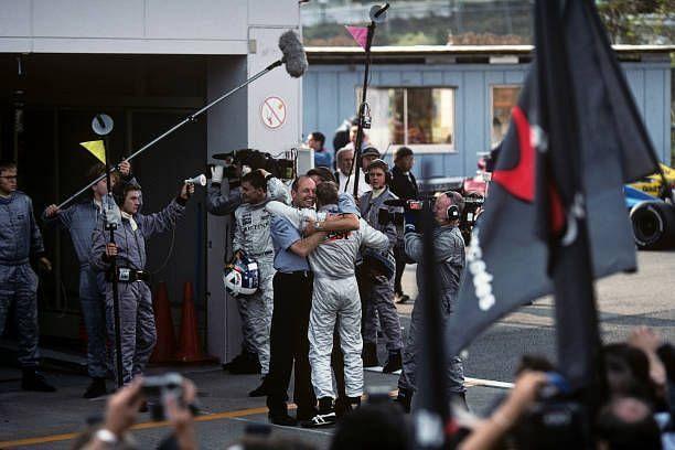 Ron Dennis and Mika Hakkinen hug in the paddock after the Suzuka win