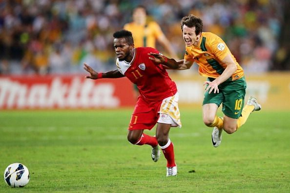 Saad Al-Mukhaini of Oman in red jersey against Australia during the FIFA World Cup Asian Qualifier