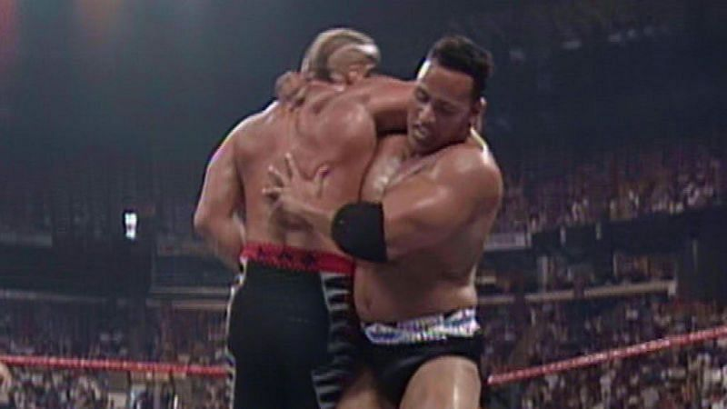 Nation of Domination member Rocky Maivia (The Rock) prepares to plant Road Warrior Hawk with his finisher.