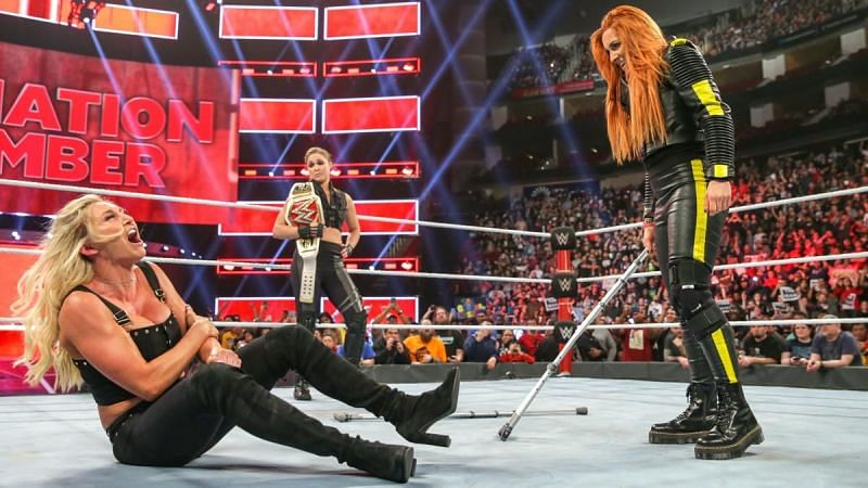 Becky Lynch attacking Charlotte Flair while Ronda Rousey looks on
