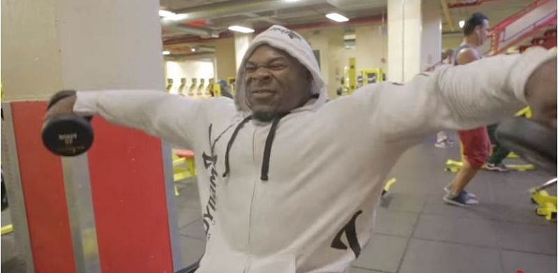 Kai Greene performing the side lateral raise with internal rotation at the top of the movement