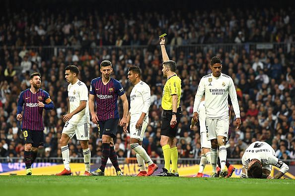 Clement Lenglet being shown a yellow card for his challenge on Sergio Ramos.