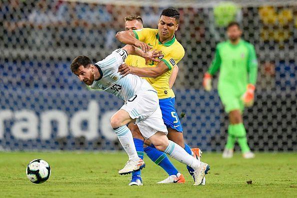 Casemiro holds Messi down.