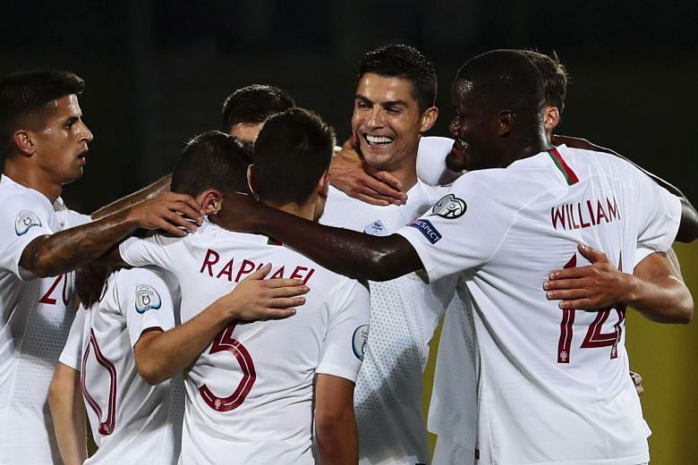 Portugal players rejoice after scoring a goal against Lithuania