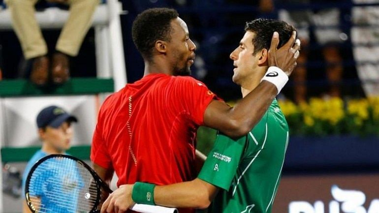Monfils (right) greets Djokovic at the net following their semifinal