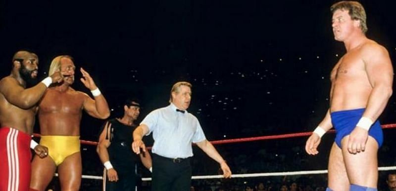 Hulk Hogan, flanked by 1980s film star and cult of personality Mr. T, faces off against Rowdy Roddy Piper at the first Wrestlemania.