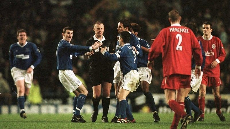 Everton players surround the referee during the Merseyside derby