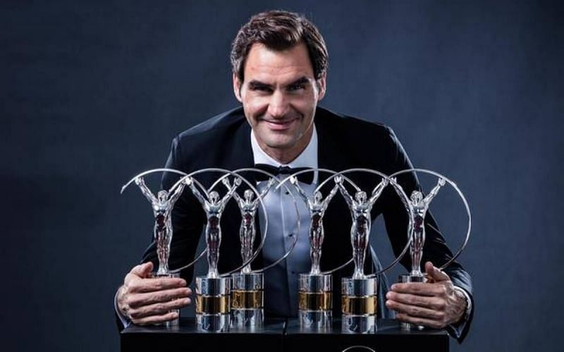 Roger Federer poses with his record six Laureus trophies