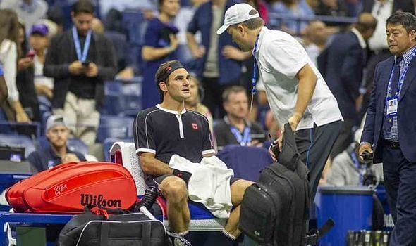 Roger Federer receives back treatment during his quarterfinal match at the 2019 US Open