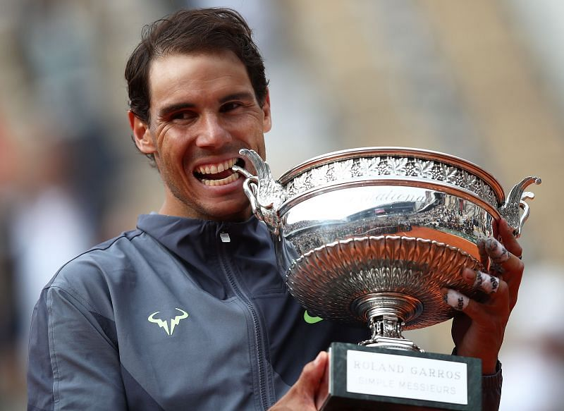 Rafael Nadal takes a bite of the 2019 Roland Garros trophy.