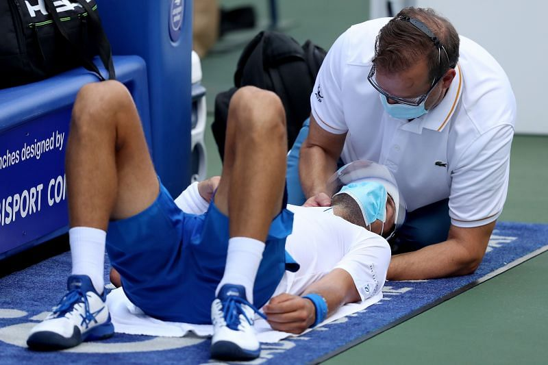 Novak Djokovic receives treatment to his neck during the semifinals