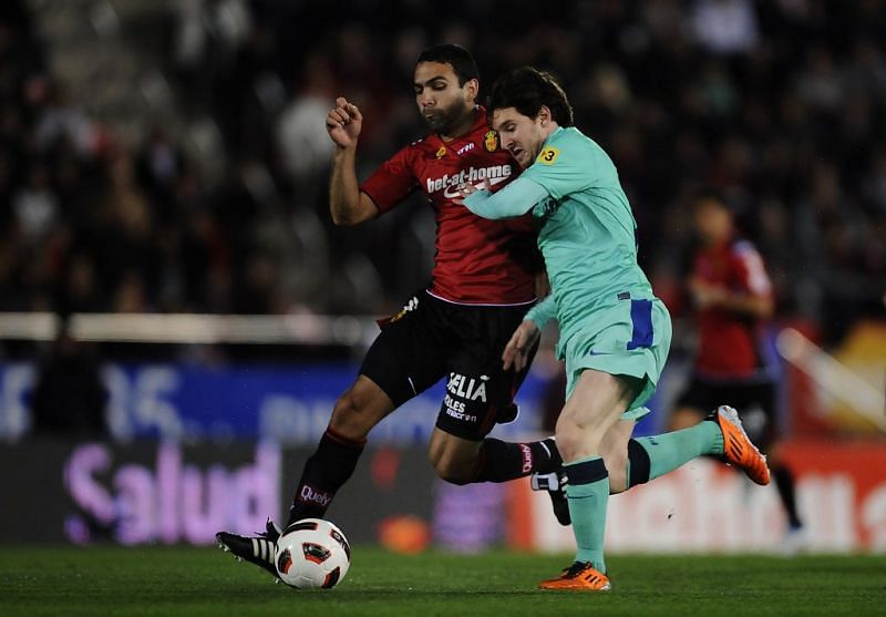 Joao Victor in a tussle with Lionel Messi