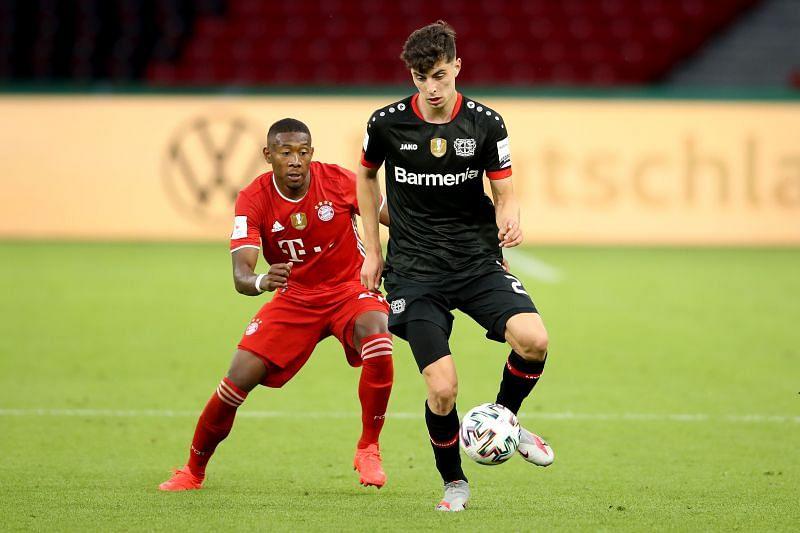 David Alaba (L) of Bayern Muenchen battles for the ball with Kai Havertz of Leverkusen