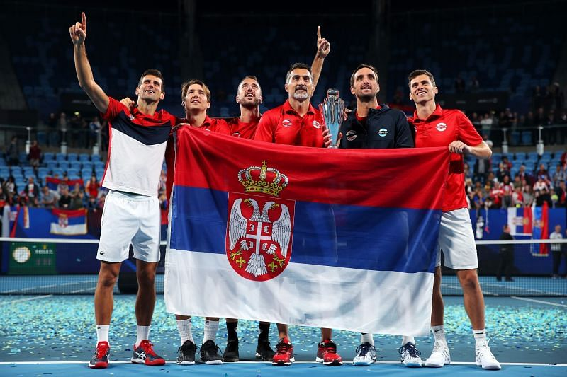 Novak Djokovic poses with the Serbian flag after winning 2020 ATP Cup