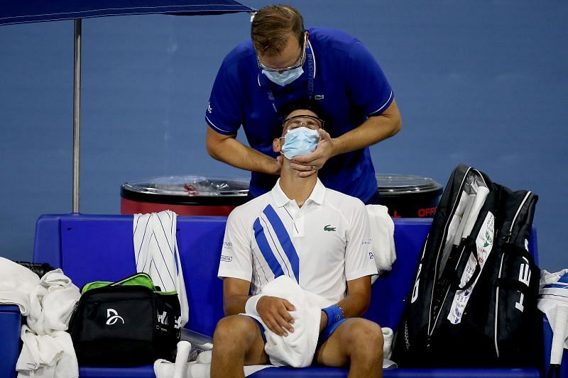 Novak Djokovic receives a treatment for his neck pain