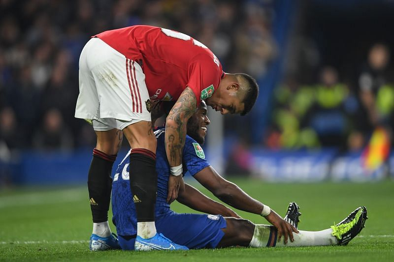 Michy Batshuayi of Chelsea is helped up by Marcos Rojo of Manchester United