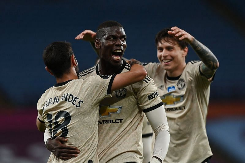 Paul Pogba celebrating a goal with Bruno Fernandes (left) and Victor Lindelof (right)