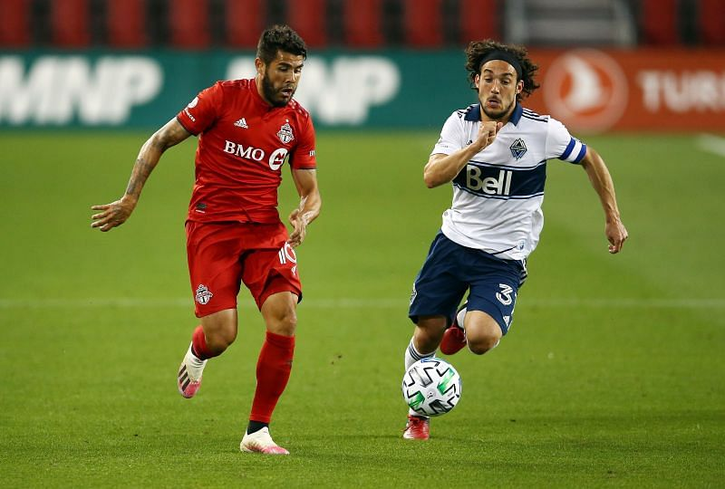Alejandro Pozuelo of Toronto FC battles for the ball with Russell Teibert of Vancouver Whitecaps