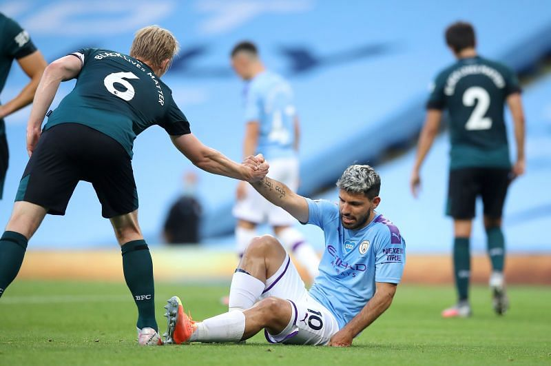 Ben Mee of Burnley gives a helping hand to Sergio Aguero of Manchester City