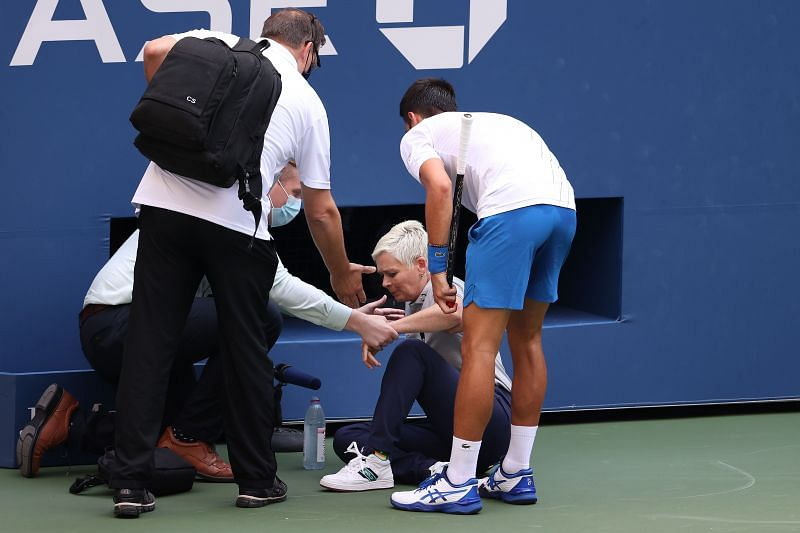 Novak Djokovic checks on the lineswoman after the accident.