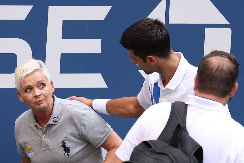 Novak Djokovic tends to the line judge