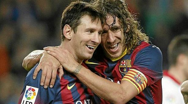 Lionel Messi (left) with former Barcelona player Carles Puyol (right)