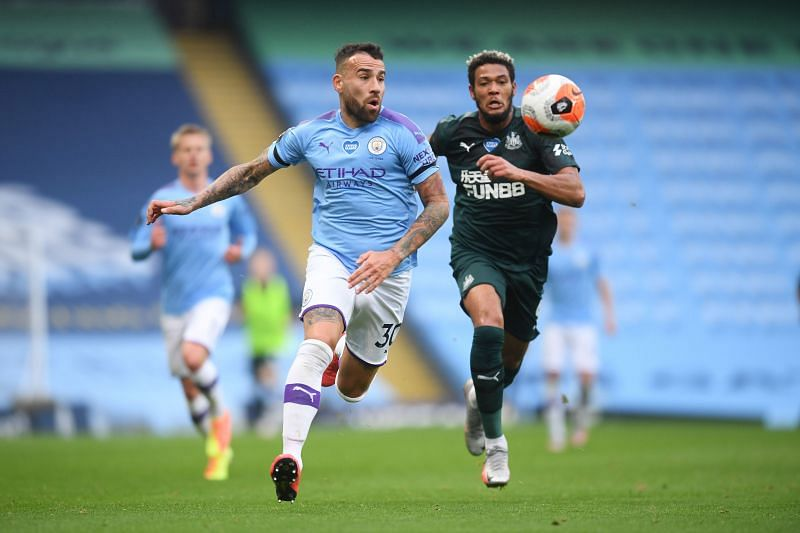 Nicolas Otamendi of Manchester City battles for possession with Joelinton of Newcastle