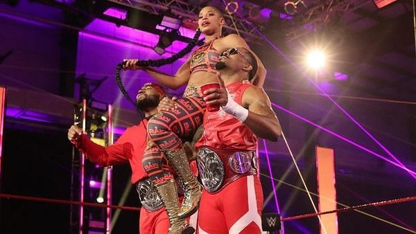 Bianca Belair in WWE with the current WWE RAW Tag Team Champions, The Street Profits