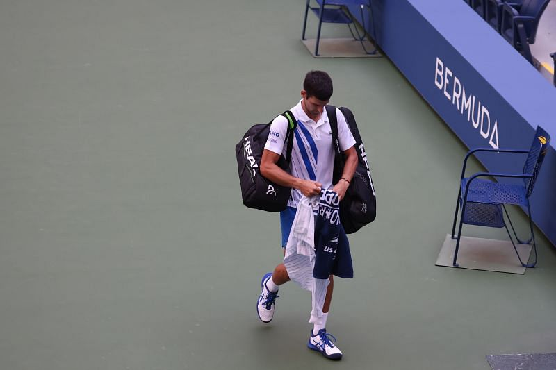 Novak Djokovic leaves the court after being defaulted