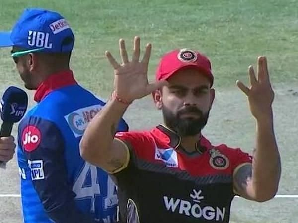 Virat Kohli signalling to his team after a toss in a different game