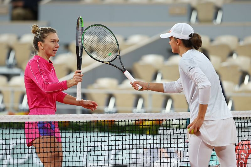 Iga Swiatek knocks racquets at the net with Simona Halep after their fourth round match at the French Open