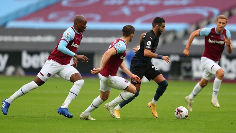 Riyad Mahrez of Manchester City runs with the ball surrounded by West Ham United players