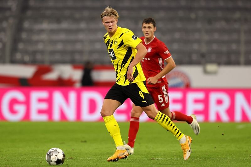 Haaland of Borussia Dortmund runs with the ball during the game as Benjamin Pavard looks on.