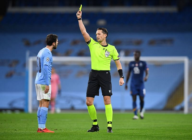 Match Referee Andris Treimanis shows a yellow card to Bernando Silva.