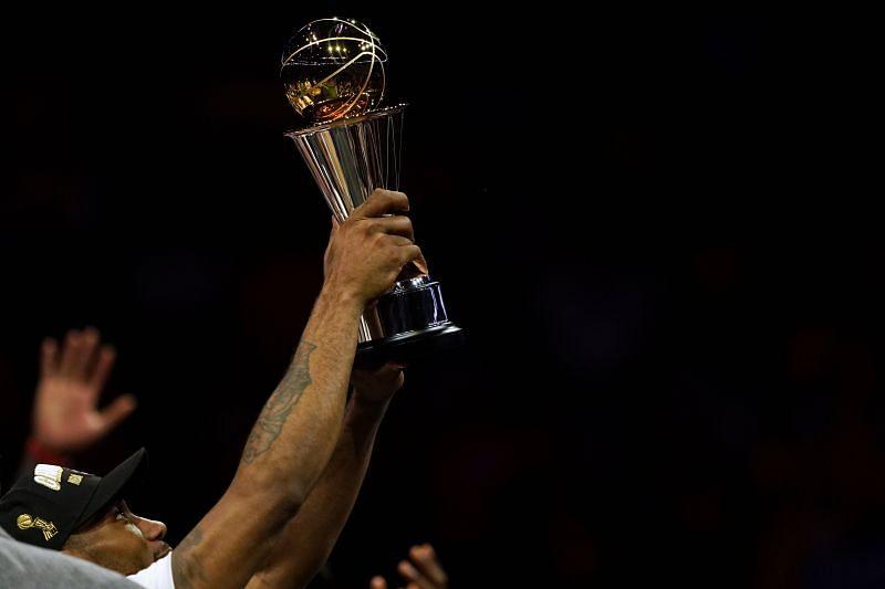 Kawhi Leonard holding the Bill Russell NBA Finals MVP award in 2019.