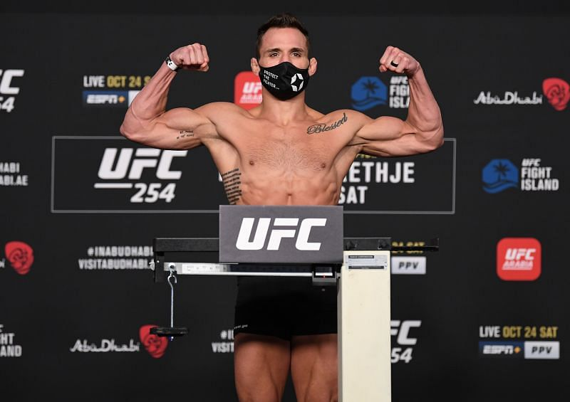 Michael Chandler poses on the scale during the UFC 254